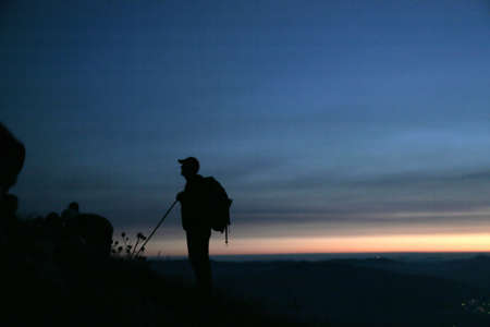 Mountaineer waiting for sunrise at the top of the mountain photo
