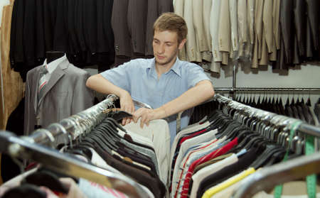 The young man chooses to itself clothes in a supermarket.
