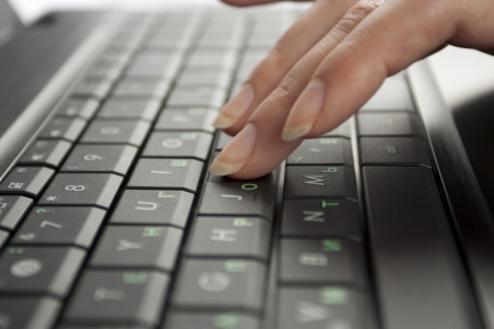 Fingers of a female hand which concern laptop keyboards