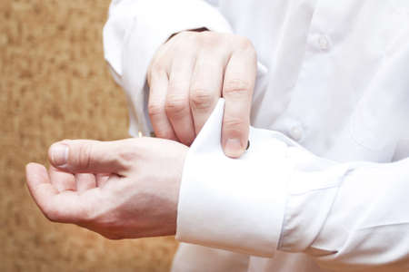 The man clasps cuff links on a white shirt Stock Photo