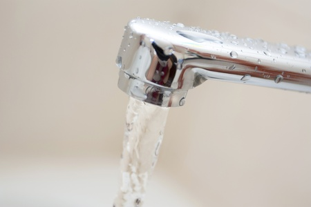 Current of water with under the covered chrome of the crane in a bathroom