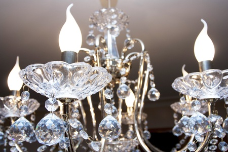 Crystal chandelier with the included bulbs against a wall Standard-Bild