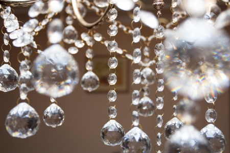 ceiling lamps: Crystal chandelier with the included bulbs against a wall Stock Photo