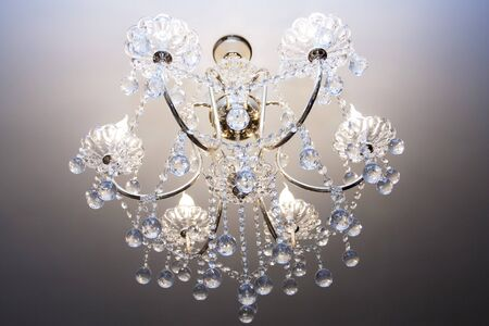 Crystal chandelier with the included bulbs against a wall photo