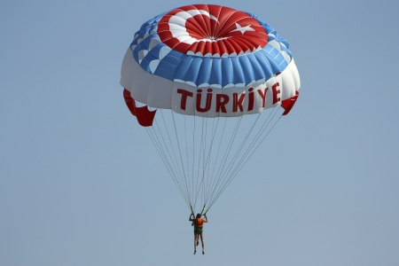 The tourist on a parachute with to Turkish symbolics in the blue sky Standard-Bild