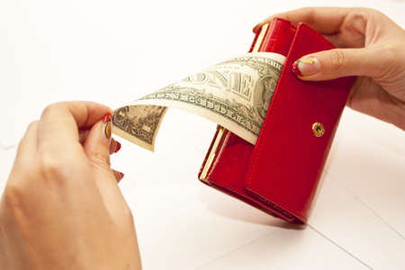 Red purse in hands with dollar on a white background