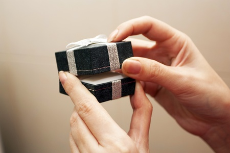 unexpectedness: Gift box with a bow in female hands