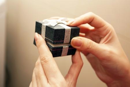 unexpectedness: Caja de regalo con un lazo en manos femeninas