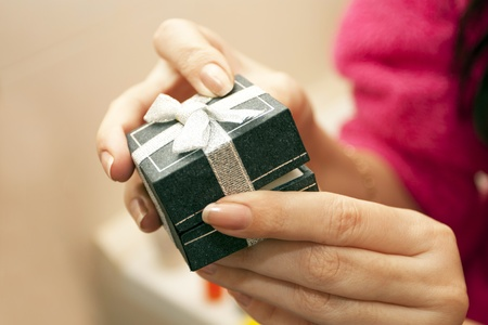 Gift box with a bow in female hands photo