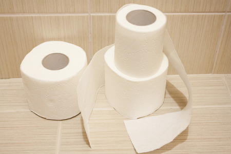 The unwound rolls of white toilet paper with texture in a toilet Stock Photo