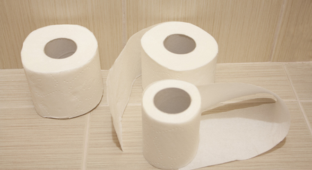 unwound: The unwound rolls of white toilet paper with texture in a toilet Stock Photo