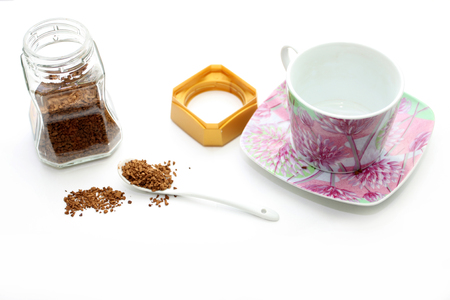 Porcelain cup and jar with instant coffee on a white background photo