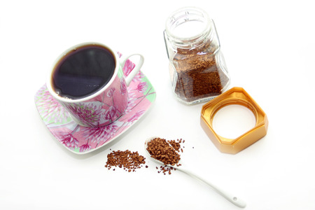 Open glass jar and cup with instant coffee on a white background photo