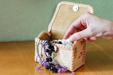 costume jewelry: Female hand takes jewelry, costume jewelry of yellow wicker boxes