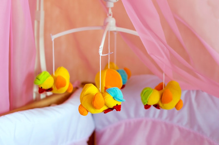 Musical roundabout with soft toys, mobile  in a crib in the room photo