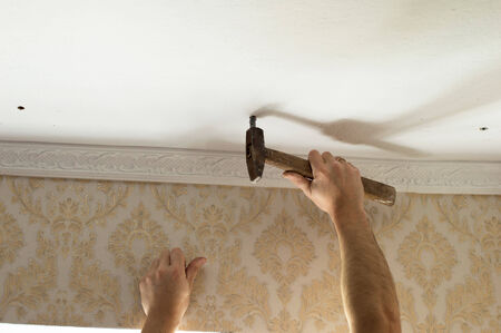 dowel: The process of driving hammer the plastic anchors into the ceiling Stock Photo