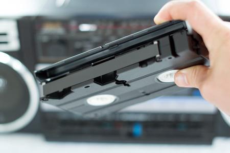 videotape: Plastic, black videotape in hand on blurred background Stock Photo