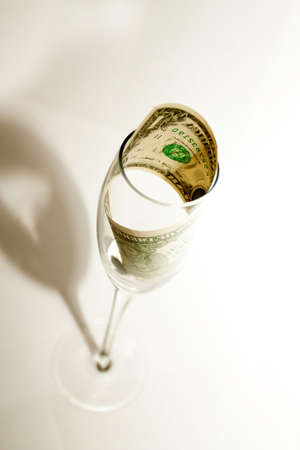 wastes: One dollar in a crystal glass on a white background