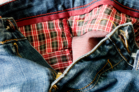 Unbuttoned blue jeans with red fabric lining