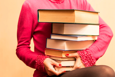 A large number of books in the hands of women on a yellow background photo
