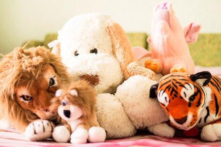 for children toys: Different soft toys for children on the couch in the bedroom