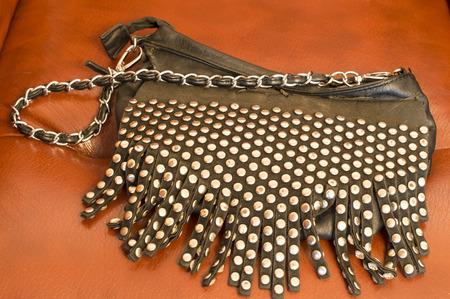 brown leather sofa: Borsa delle donne alla moda con pietre decorative su uno sfondo di divano in pelle marrone