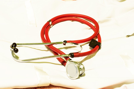 Medical stethoscope of red light against a white dressing gown of the doctor photo
