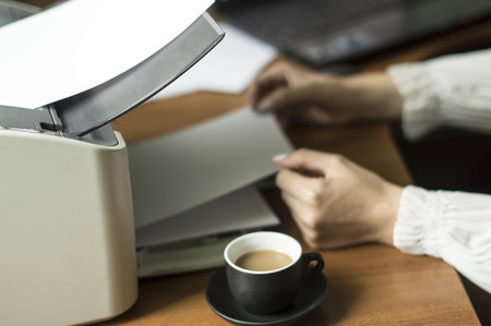 The process of inserting paper in laser printer cartridge on an Office background photo
