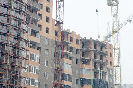 The process of the construction of a new brick house with the help of cranes on time snowfall photo