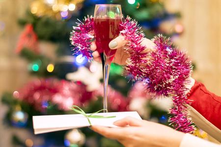 glas sekt: Weihnachtsthema-ein Glas Rot Sekt in eine weibliche Hand mit Weihnachtsbaum mit Schmuck Lizenzfreie Bilder