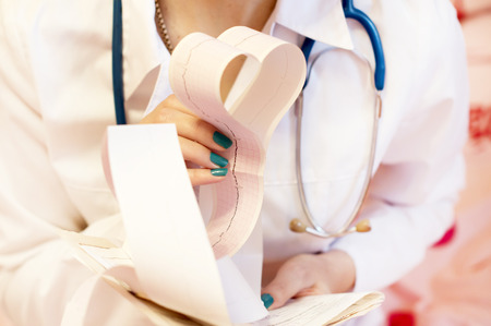 A doctor with a stethoscope and white coat with cardiograms in his hands in the shape of a heart photo
