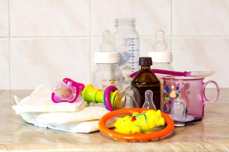 fondo para bebe: Botella de cristal con la mezcla de alimentación, juguetes y pañales para bebé en la encimera de la cocina