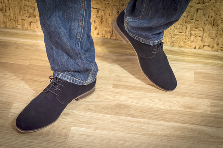 walk in closet: Presentation of new models of mens suede shoes against a wall with wallpaper and wooden parquet