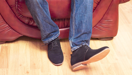 walk in closet: Presentation of new models of mens suede shoes on the background near the leather chairs and wooden flooring