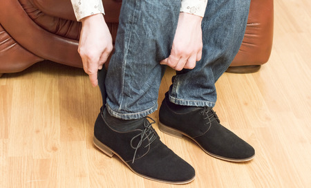 walk in closet: The process of wear black suede shoes in the room on the couch Stock Photo