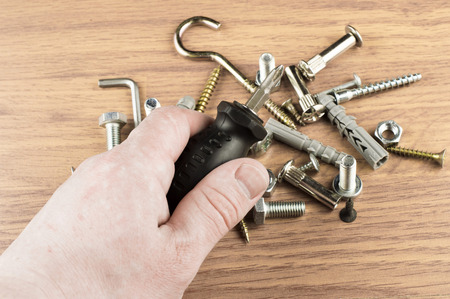 mounting: Screwdriver in the hand of the master on the background of various bolts and dowels for mounting and fastening Stock Photo