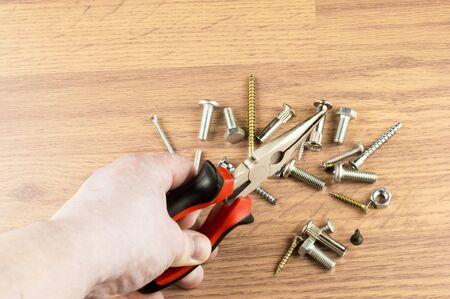 mounting: Pliers in the hand of the master on the background of various bolts  for mounting and fastening