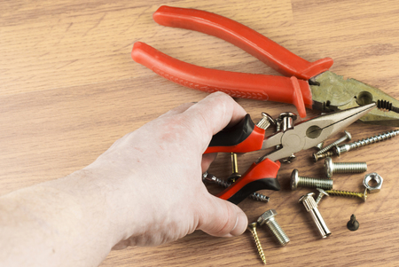 mounting: Pliers in the hand of the master on the background of various bolts and dowels for mounting and fastening Stock Photo