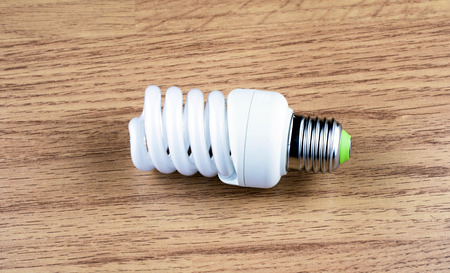 economical: spiral luminescent economical lamp on background wooden floor
