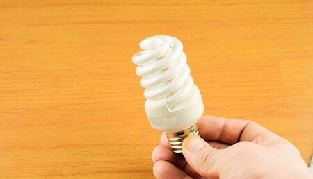 luminescent: Luminescent light bulb in his hand on a background texture of wood Stock Photo