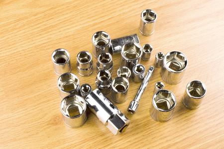 tighten: Set of different nozzle to tighten the bolts on the background of the wooden floor Stock Photo