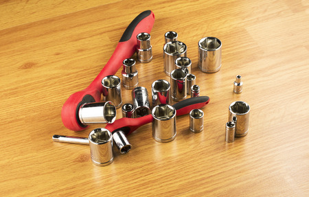 tighten: Ratchet and a set of different attachments to tighten the bolts on the background of the wooden floor Stock Photo