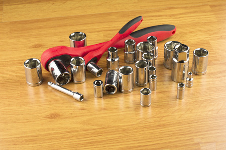 ratchet: Ratchet and a set of different attachments to tighten the bolts on the background of the wooden floor Stock Photo