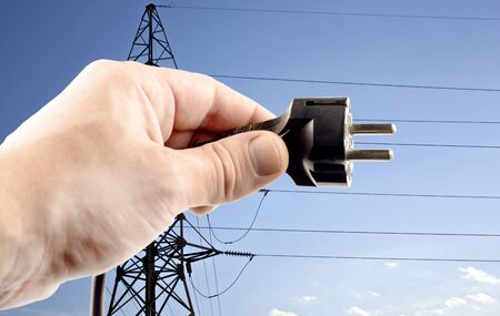 mains: Shtepsel in your hand on a blue background power lines