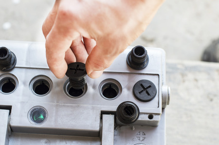 unscrewing: The process of unscrewing stoppers in car battery