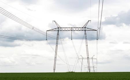 against the current: power transmission lines against the sky and green field Stock Photo