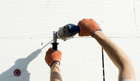 polyfoam: The process of drilling holes in the white polyfoam of using electric drills Stock Photo