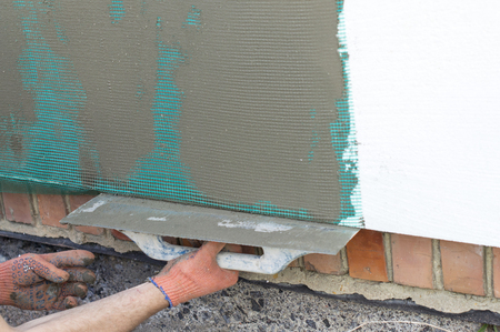 polyfoam: The process of applying putty to the  polyfoam wall using a spatula Stock Photo