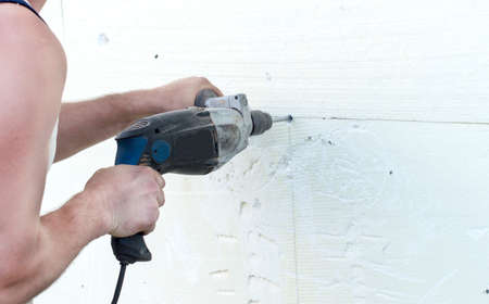polyfoam: The process of drilling holes in the white polyfoam of by using electric drills Stock Photo