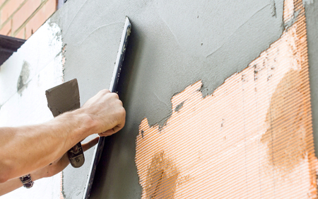 putty: The process of putty the walls with a large spatula Stock Photo